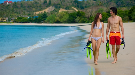 Couple on beach with snorkel equipment